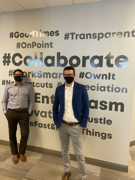While the GrantMatch team continues to work remotely during the COVID-19 pandemic,  Managing Partners Dan Civiero, (left), and Mike Janke are pictured here  in front of the GrantMatch culture wall at the firm's head office during a recent visit
